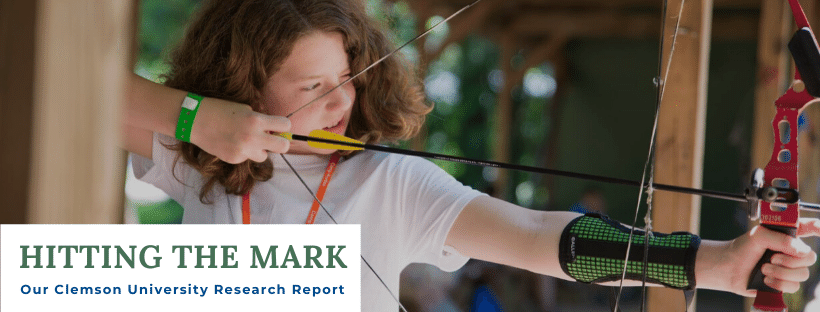 "A Kudzu camper draws her bow and aims an arrow at an offscreen target. A title is overlaid on the lower left corner that says ""Hitting the Mark: Our Clemson University Research Report."""