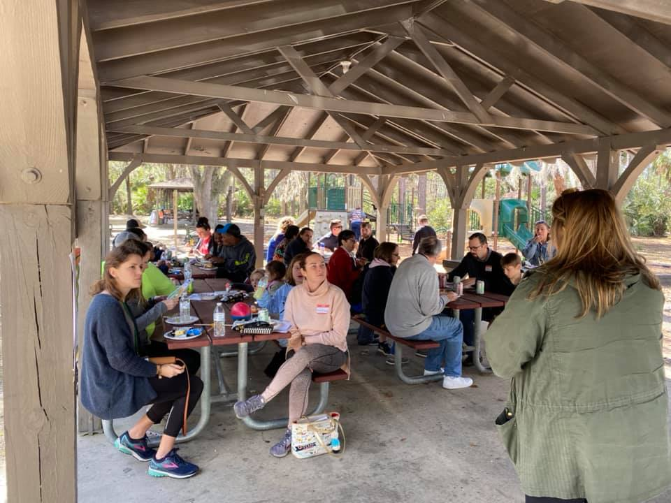 Several attendees of the Camp Kudzu Cookout sit at tables and listen to a speaker giving a presentation.